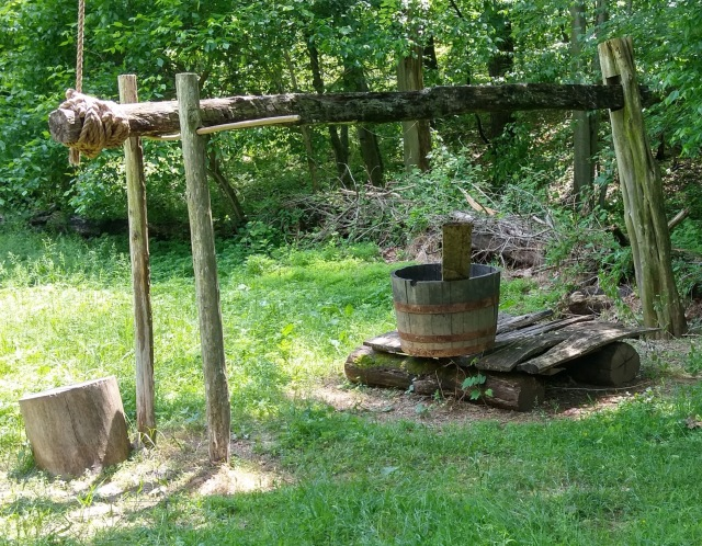 A very old water well with a wooden bucket