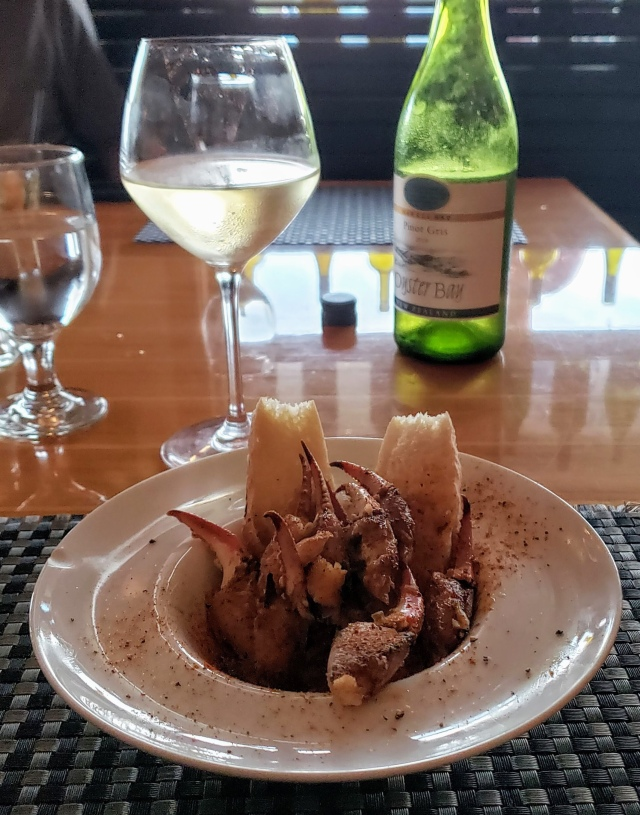 Bowl of crab claws with a glass and bottle of wine in the background