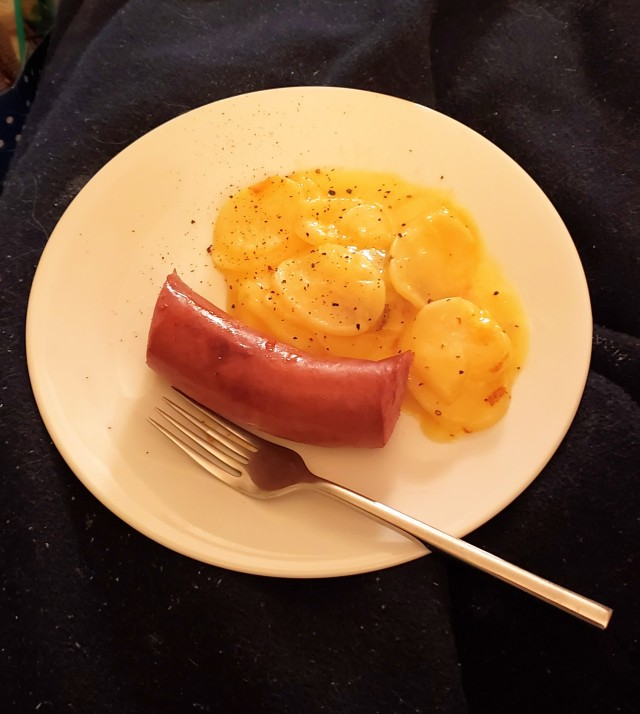 A white plate with a piece of kielbasa and a side of cheesy potatoes