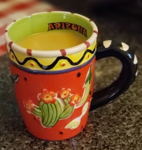 A red latte mug with flowering cactus and yellow trim