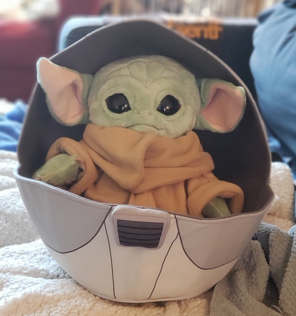 A Baby Yoda plush, in a space pram