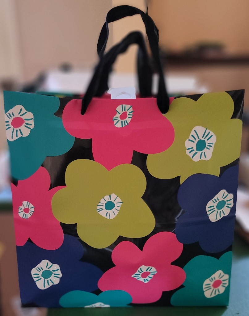 A gift bag with flowers on it with candy inside