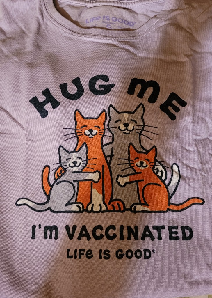 T-shirt with cartoon cats hugging that says Hug Me I'm Vaccinated