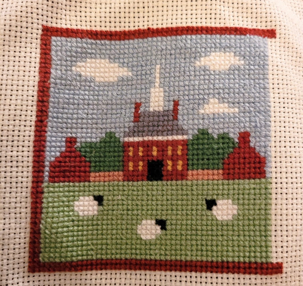 Work In Progress Cross Stitch of the Governors Palace in Williamsburg VA - the main building, grass, sky, and little sheep are stitched in