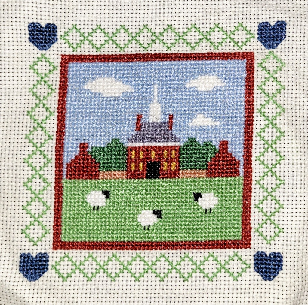 Finished cross stitch of the Governors Palace with sheep on the lawn in Williamsburg VA