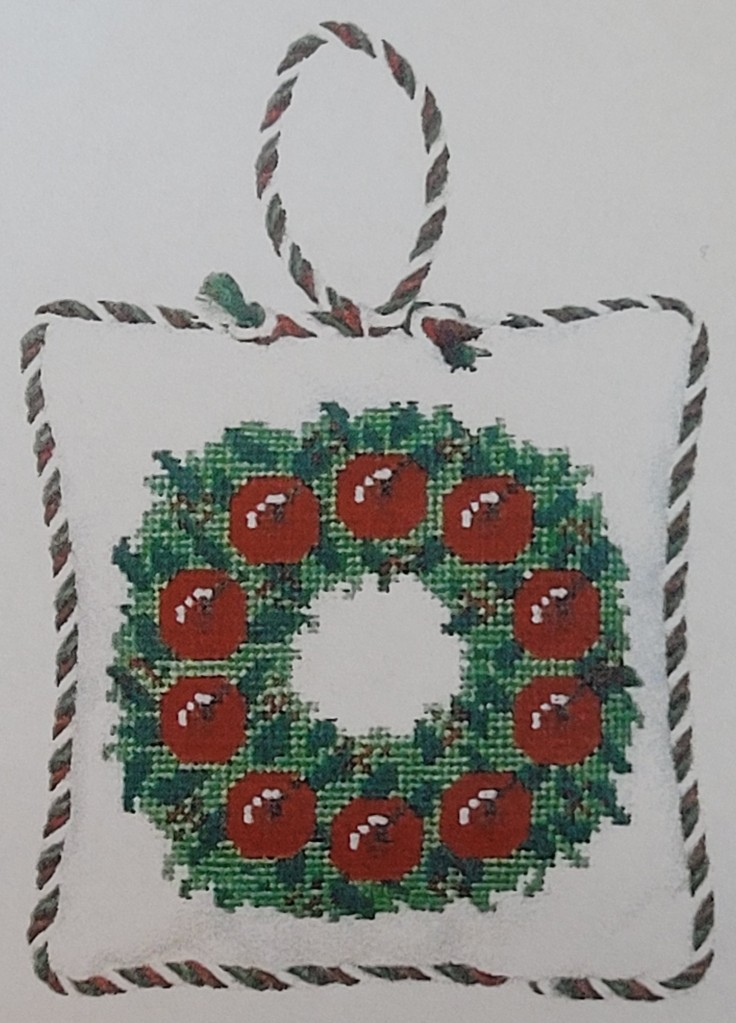 Cross stitch of a green wreath with red apples