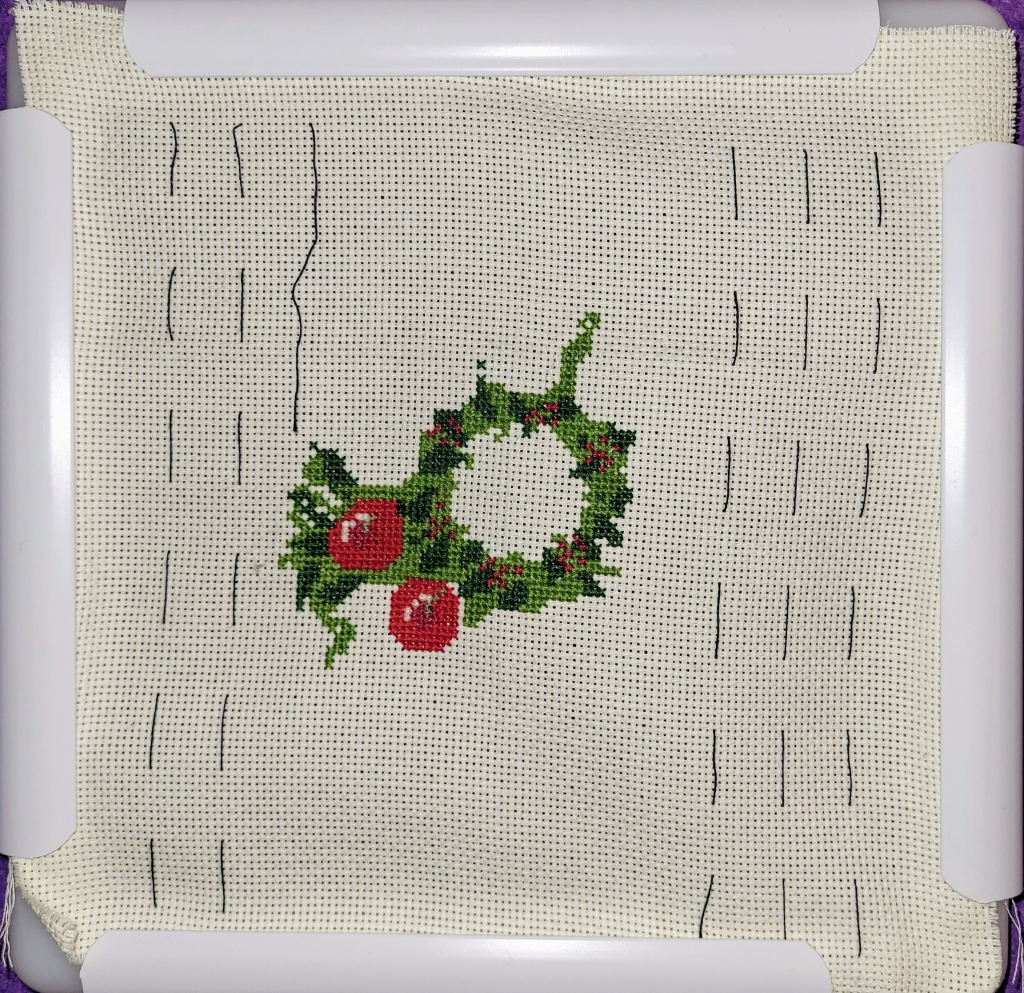 Work in Progress of Christmas wreath cross stitch, center done and two apple added in the lower left