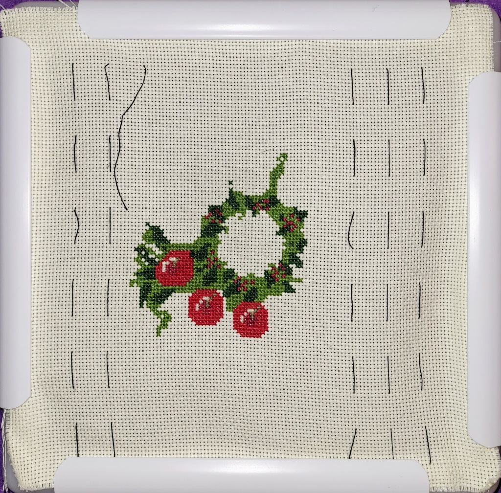 Work in Progress of Christmas Wreath cross stitch - center ring of greens done, with 3 apples