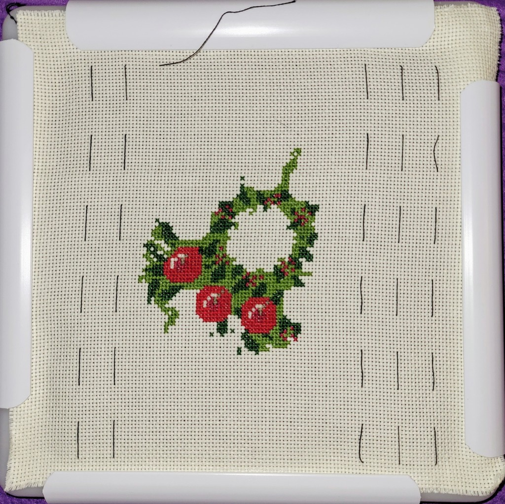 Christmas wreath cross stitch - center ring done, 3 apples stitched in and more green at the bottom