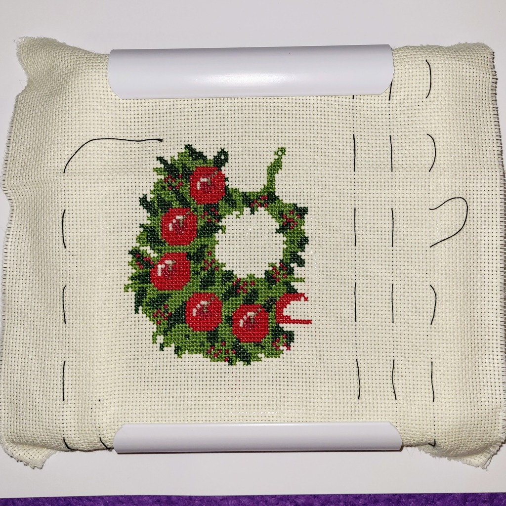 Work in progress of Christmas wreath cross stitch, about halfway done